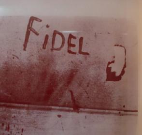 El miliciano Eduardo García Delgado, víctima del criminal bombardeo en las bases aéreas cubanas, escribe con sangre el nombre de Fidel, el 15 de abril de 1961.