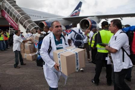The first members of a team of 165 Cuban doctors and health workers unload boxes of medicines and medical material from a plane upon their arrival at Freetown's airport to help the fight against Ebola in Sierra Leone, on October 2, 2014.